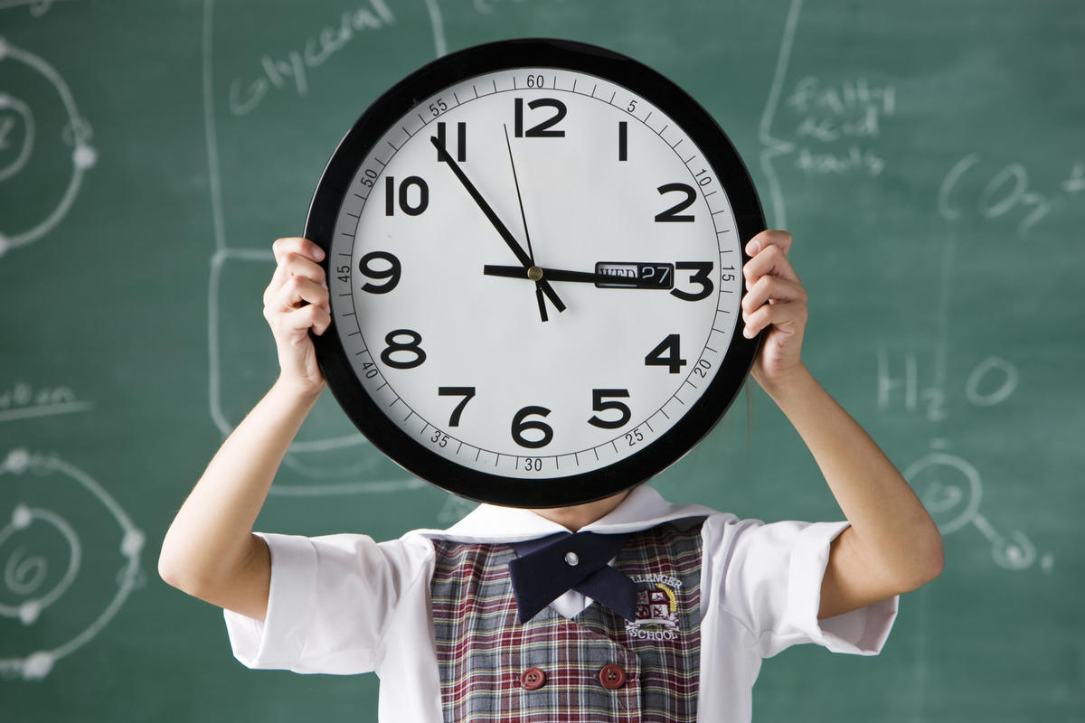 girl in a classroom holding a clock in front of her face